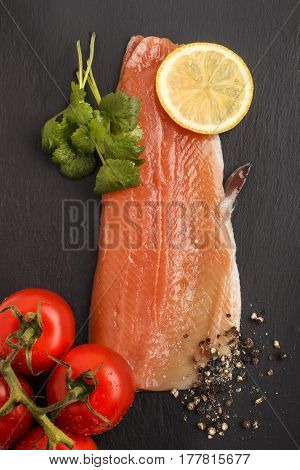 raw trout fillet with slice lemon wet tomato crushed peppercorn and fresh coriander on slate