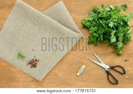 Bunch of parsley is on linen napkin on light brown wooden background. Focus is on parsley. Copy-space composition