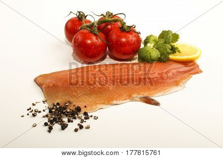 raw trout fillet with slice lemon wet tomato crushed peppercorn and fresh coriander on white