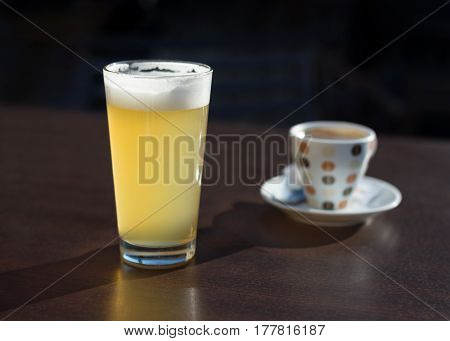 glass of beer and a cup of coffee on the cafe table