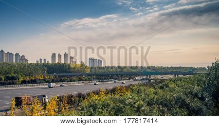 Beijing, China - Oct 31, 2016: High-rise apartments and a wide multi-lane highway scene captured from within a High-Speed Rail (HSR) bullet train traveling at 300 km/h.