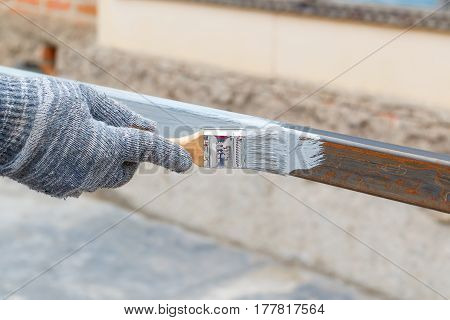 Right hand in rag glove paint brush steel post in gray anti rust paint. Half - painted surface. Smear of paint brush