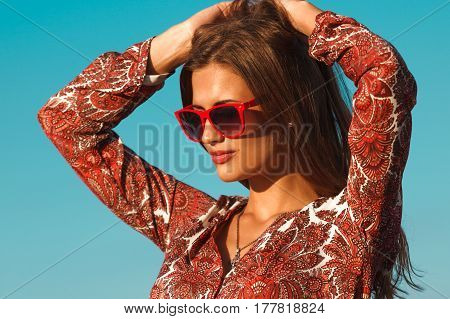 Fashion woman portrait wearing red sunglasses over the blu sky background