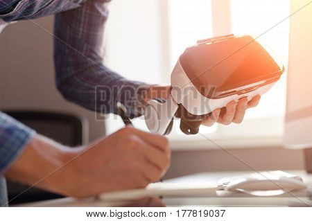Hands of a person taking the notes and holding the virtual reality goggles.