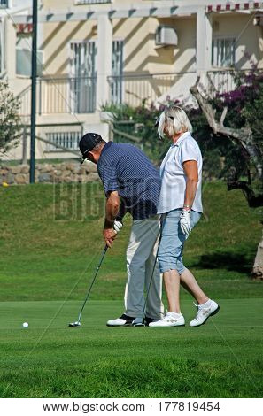 CALETA DE VELEZ, SPAIN - OCTOBER 27, 2008 - Couple playing golf at Los Llanos de Baviera Golf Caleta de Velez Malaga Province Andalusia Spain Western Europe, October 27, 2008.