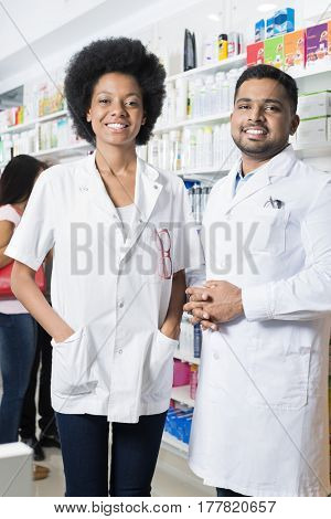Confident Male And Female Pharmacists In Pharmacy