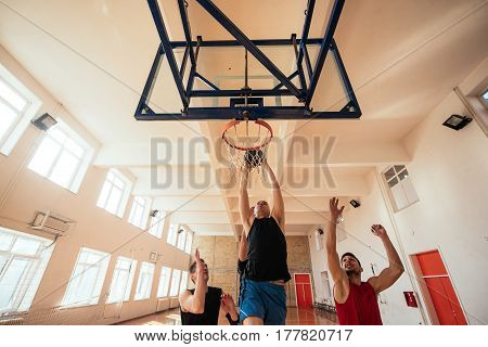 Photo of basketball players scoring a point indoors.