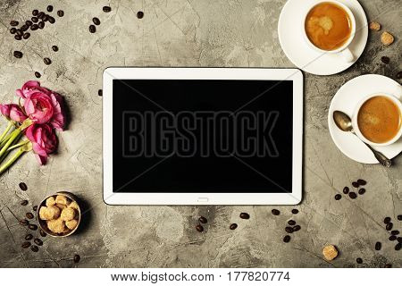 Tablet, coffee and beautiful flowers on grey stone background. Top view. Flat lay style.