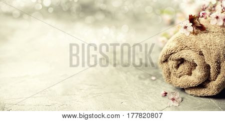 Spa setting. Towel, spring flowers and sea salt on rustick background