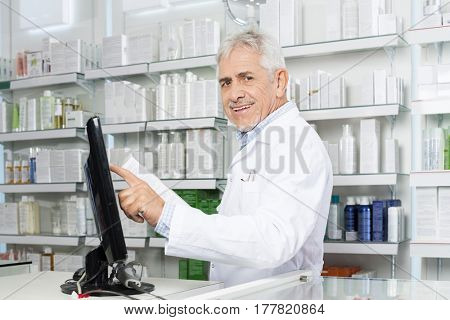 Smiling Pharmacist Touching Monitor Screen In Pharmacy
