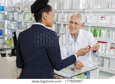 Chemist Holding Prescription Paper While Looking At Businesswoma