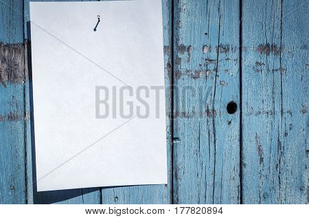 blank white piece of paper hanging on a nail on a blue wooden wall