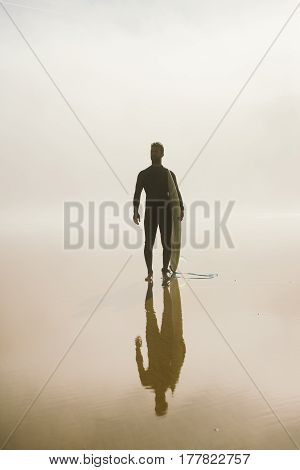 Young Man Ready For Surfing On A Misty Morning