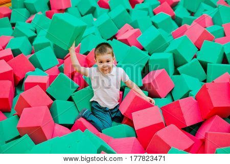 The boy throws himself in a dry pool with bright soft bright cubes