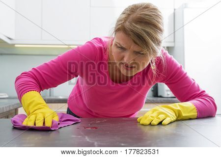 Woman clening a stain on kitchen counter