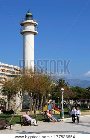 TORRE DEL MAR, SPAIN - OCTOBER 27, 2008 - View of the lighthouse and childrens playground along the promenade with tourists enjoying the setting Torre del Mar Malaga Province Andalusia Spain Western Europe, October 27, 2008.