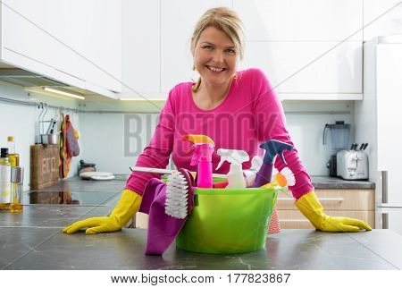 Happy housewife with cleaning supplies standing in kitchen