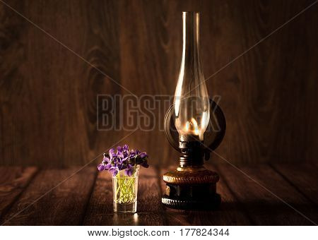 Spring Concept With Violet And Oil Lamp On Wooden Table