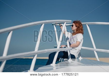 Beautiful ginger woman in sun glasses sits on a white yacht in a sea with clear turquoise water. Relaxation at summer vacation under a sun.