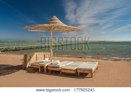 Sun lounger under the beach umbrella with view at the sea coast. Blue sky and white clouds over a resort beach. Wooden shore-arm over the sea.
