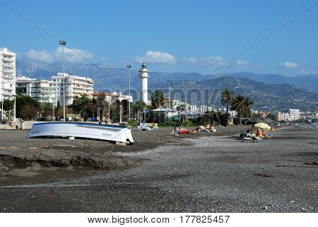 TORRE DEL MAR, SPAIN - OCTOBER 27, 2008 - View along the beach towards the lighthouse with a boat in the foreground Torre del Mar Malaga Province Andalusia Spain Western Europe, October 27, 2008.