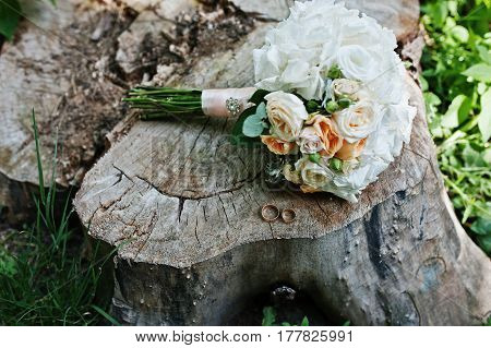 Tenderness Wedding Bouquet With Pink, Orange And White Roses & Wedding Rings At Stump On Wood.