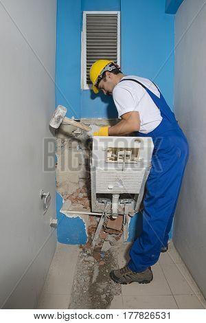 Construction Worker Demolishing Flush Toilet