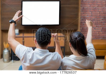 Two asian couple see the television on sofa in family room in home TV and green screen blue screen concept
