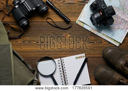 Top view flat lay of a travel set consisting of bag, binoculars, old hiking boots, map, photo camera, pocket flashlight, magnifying glass and small notebook over wooden planks