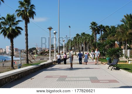 TORRE DEL MAR, SPAIN - OCTOBER 27, 2008 - Tourists walking along the promenade with the beach to the left Torre del Mar Malaga Province Andalusia Spain Western Europe, October 27, 2008.