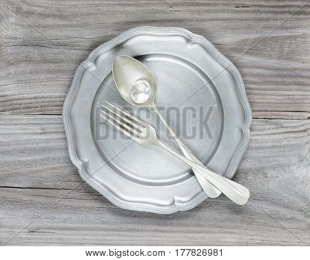 Big diamond vintage fork and spoon in an empty tin plate on an old wooden table