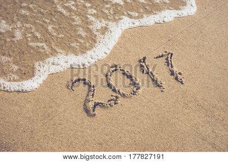 Year 2017 written in sand on a sea beach