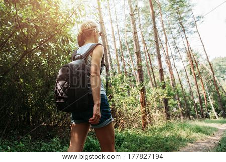 Young active woman hiking across natural park on the trail. Female backpacker traveling in summery forest.