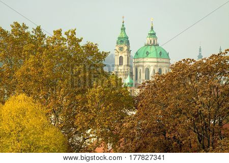 Dome of St Nicholas Church (Cathedral) surrounded by autumn tree tops of Mala Strana Prague Czech Republic.