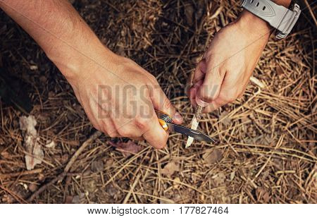 Close-up of male hiker hands sharpen stick with knife on the ground. Concept of travel, extreme and survival.