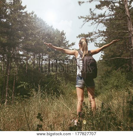 Venture, goal and success. Young sporty woman trekker standing in wild wood with outstretched arms at sunlight.