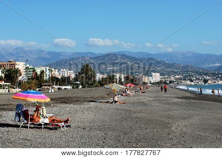 TORRE DEL MAR, SPAIN - OCTOBER 27, 2008 - View along the beach with mountains to the rear and tourists sunbathing Torre del Mar Malaga Province Andalusia Spain Western Europe, October 27, 2008.