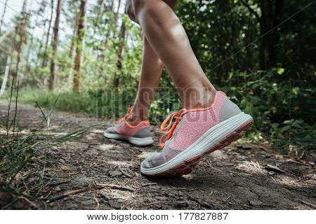 Close-up of female hiker in sport shoes traveling through natural park. Vacation, tourism and discovery concept.
