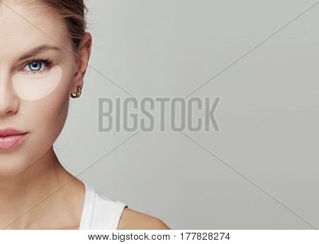 Close-up portrait of young pretty woman with underlined eye contour, area of black eye and first mimic wrinkle. Concept of anti-age cosmetics, treatment and skincare.