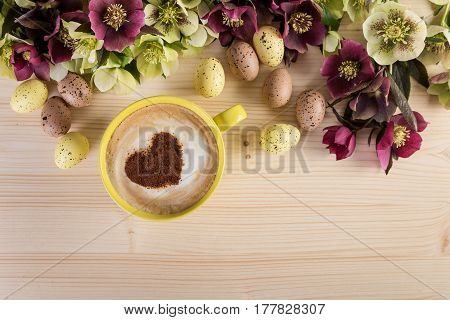 Coffee cup Cappuccino with Easter decoration on light wooden table. Heart shape foam top view.