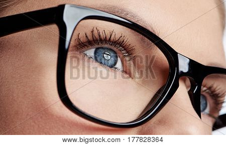Close-up of female blue eye wearing spectacles with black frame. Concept of human vision, sight examination and care.