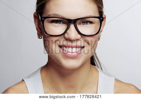 Young smiling woman in optical eyeglasses. Optometry and eyes correction concept.