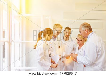 Doctors in team during meeting as group communicating with tablet