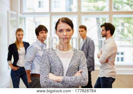 Woman with crossed arms as start-up founder in front of business people