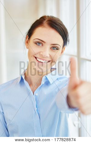 Young woman holding thumbs up as sign of motivation