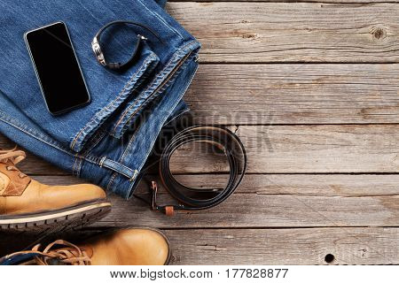 Men's clothes and accessories. Jeans, shoes, belt, smartphone on wooden background. Top view with copy space