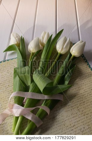 White tulips on white wooden background. Compilation of a bouquet