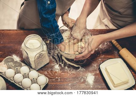 Cropped image of cute little girl and her beautiful mom in aprons kneading the dough in the kitchen