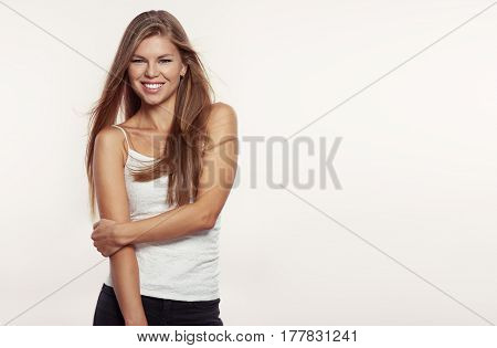 Pretty smiling woman model in street fashion outfit with windy hair posing in studio. Space for text or advertising on background.