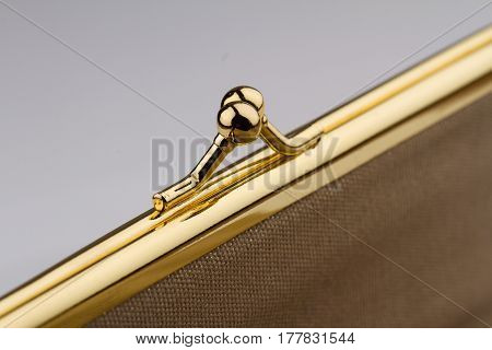 macro detail of closed female cream colored vintage wallet with golden metal enclosure on grey background